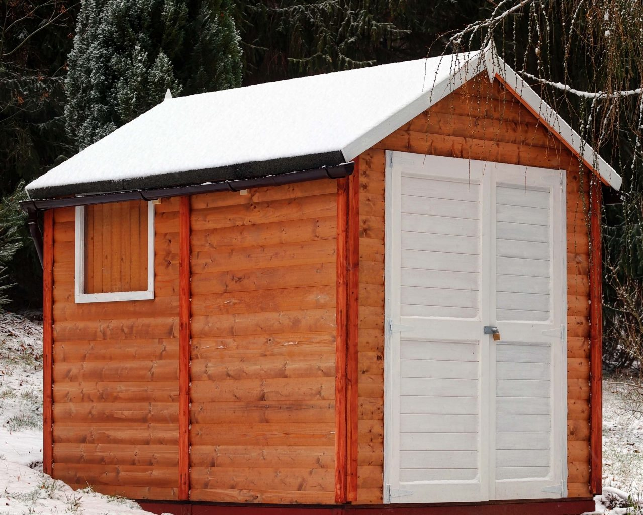 a log cabin shed with a white door and red trim